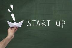 Start, neues Geschäftskonzept Menschliche Hand, die Papierschiff gegen die grüne Tafel mit Text hält: START Stockbilder