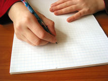 Start new page. Closeup on the hands of a child starting to white on the new blank page, space for copy royalty free stock images