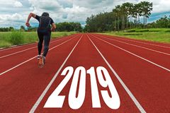 The start into the new year 2019. Start up of runner man running on race track go to Goal of Success, people running as part of Nu. Mber 2019, copy space royalty free stock photo
