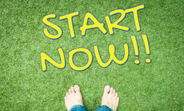 Start now concept text with human foot on grass Stock Photo