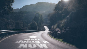 Start now!. Long deserted road through mountains with concept words start doing it now and arrow on asphalt royalty free stock photos