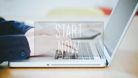 Start Now, text over young man typing on laptop at desk Royalty Free Stock Photos