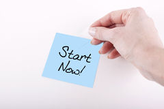 START NOW. Woman hand taping START NOW note on white surface Royalty Free Stock Images
