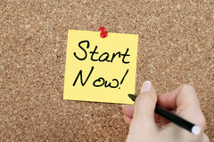 START NOW. Woman hand writing START NOW on yellow paper pinned on cork noticeboard Stock Image