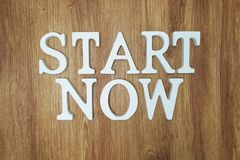 Start Now Word alphabet letters on wooden background. Start Now Word alphabet letters with space copy on wooden background royalty free stock photo