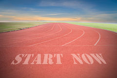 Start now written on Running track with green grass and blue sky Stock Photos