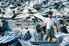 Start Over. A young Laotian boy searches for water or anything he can salvage after a fire destroyed almost the entire refugee camp, at Nong Khai, Thailand, 1980 Stock Photo