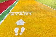 The start point on the yellow running lane in the park royalty free stock photography