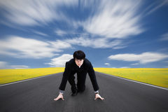 Start a race. Young asian businessman kneeling as if about to start a race royalty free stock images