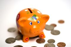 Start saving. Little toy piggybank with some coins around it Stock Images
