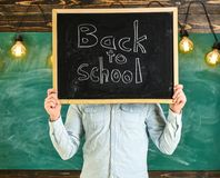 Start of school year concept. Teacher faceless holds blackboard with title back to school. Man welcomes students. Chalkboard on background. Teacher holds stock photography