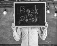 Start of school year concept. Teacher faceless holds blackboard with title back to school. Man welcomes students. Chalkboard on background. Teacher holds stock image