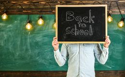 Start of school year concept. Teacher holds chalkboard in front of face. Man welcomes students, chalkboard on background. Teacher faceless holds blackboard royalty free stock images