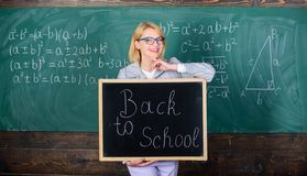 Start school year. Top ways to welcome students back to school. Teacher woman hold blackboard inscription back to school. It is school time again royalty free stock photography