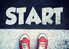 Start sign on the road. Student standing above the sign for start Stock Photography