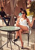 Start by smelling the aroma before tasting. Pretty woman drink coffee in outdoor cafe. Woman enjoy drinking espresso or royalty free stock photo