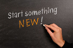 Start something NEW !. Hand writing with chalk on a blackboard Stock Photos