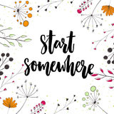 Start somewhere. Motivation saying in nature frame with twigs and flowers.  Stock Photo