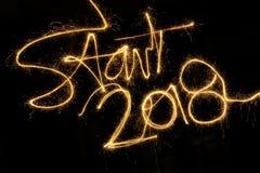 Start 2018 sparkler on a black background. Start 2018 written with a sparkler on a black background Stock Photo