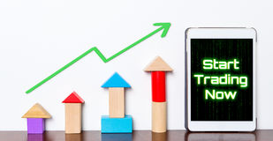 Start stock trading online on your tablet graph rising up. Stock Photo