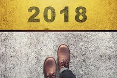 Start to do something in New Year Concept, Top view, Male with L. Eather Shoes Steps on Grunge Dirty Concrete Floor Background with word `2018 Royalty Free Stock Photos