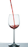 Start to pour red wine into wine glass Royalty Free Stock Images