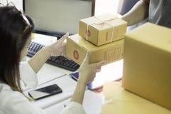 Start treft de werkende werkplaats bedrijfseigenaar voorbereidingen om goederen in kartondoos aan de leveringsmens te leveren die stock foto