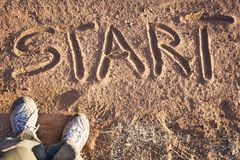 Start. Two feet on the ground and the word start written in red sand. Motivation concept for  beginning, doing and starting Royalty Free Stock Photography