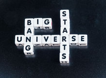 Start of universe. Text ' big bang, universe, starts ' inscribed in black uppercase letters on small white cubes crossword style , dark background Stock Images