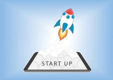 Start up business concept for mobile app development or other disruptive digital business ideas. Cartoon rocket launching from smart phone / tablet Stock Image