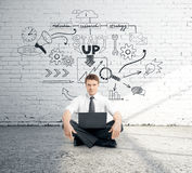 Start up concept. Businessman with laptop sitting against white brick wall with sketch. Start up concept Stock Photo