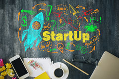 Start up concept. Start up cocnept with colorful rocket ship sketch on wooden office desktop with blank smartphone, coffee cup, stationery and other items. Mock Stock Photos