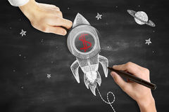 Start up concept. Male hands drawing and holding magnifier over rocket ship sketh with red dollar sign. Blackboard background. Start up concept Stock Image