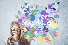 Start up concept. Portrait of attractive caucasian girl with rocket ship sketch on concrete wall background. Start up concept Royalty Free Stock Photo