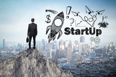 Start up concept. With rocket ship sketch and businessman looking at city from mountain top Stock Photos