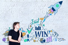 Start up concept. Side view of casual young guy pointing at creative rocket ship sketch on white brick wall background. Start up concept royalty free stock photo