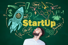 Start up concept. Surprised young man looking up at creative startup sketch on chalkboard background. Start up concept Stock Image