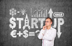 Start up concept. Young businessman thinking and drawing start up concept on concrete wall Royalty Free Stock Photos
