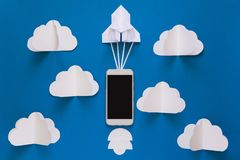 Start up or fast connection concept. The launch paper rocket with smart phone on blue sky with clouds. stock photography