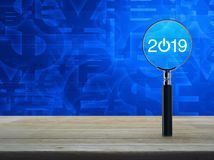 2019 start up flat icon with magnifying glass on wooden table over currency symbol blue tone background, Business happy new year stock illustration