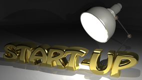 START-UP highlighted. START-UP in golden letters under the light of a desktop lamp Royalty Free Stock Photo