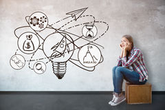Start up ideas concept. Side view of thoughtful white girl sitting on wooden box in concrete interior with rocket and lamp sketch. Start up ideas concept Stock Photo