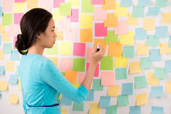 Start-up ideas. Young Asian business lady writing ideas on stick notes on the wall Stock Image
