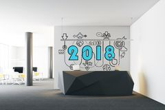 2018 and start up sketch above an office reception. 2018 and a business sketch drawn on a white wall in a modern office room above a black reception desk Royalty Free Stock Photo