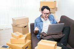 Start up small business entrepreneur SME or freelance asian man typing computer. With box, Young happy success Asian man with his hand lift up , online royalty free stock photos