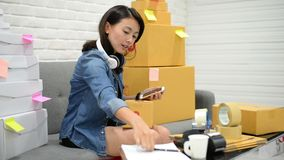 Start up small business entrepreneur SME or freelance asian woman working online market packaging with box at home concept
