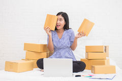 Asian woman holding boxes, online marketing packaging box and delivery. Start up small business entrepreneur SME or freelance woman working at home, in bed Royalty Free Stock Photo