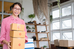 Start up small business owner holding parcel box at workplace. f. Young start up small business owner holding parcel box at workplace. freelance woman stock photography