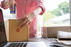 Start up small business owner packing cardboard box at workplace Stock Photos