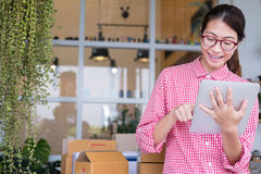 start up small business owner working with digital tablet at workplace. freelance woman entrepreneur SME seller check product royalty free stock image